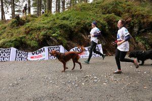 Dogrun: Bilde av to jenter som løper med hund på grusvei