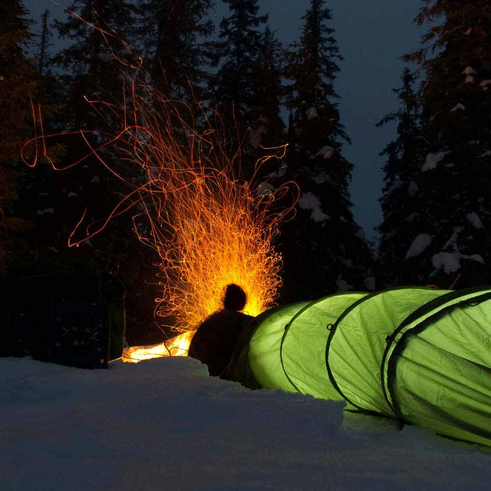 Compact allround telt (CAT): Bilde av telt en kveld i vinterlandskap med bål.